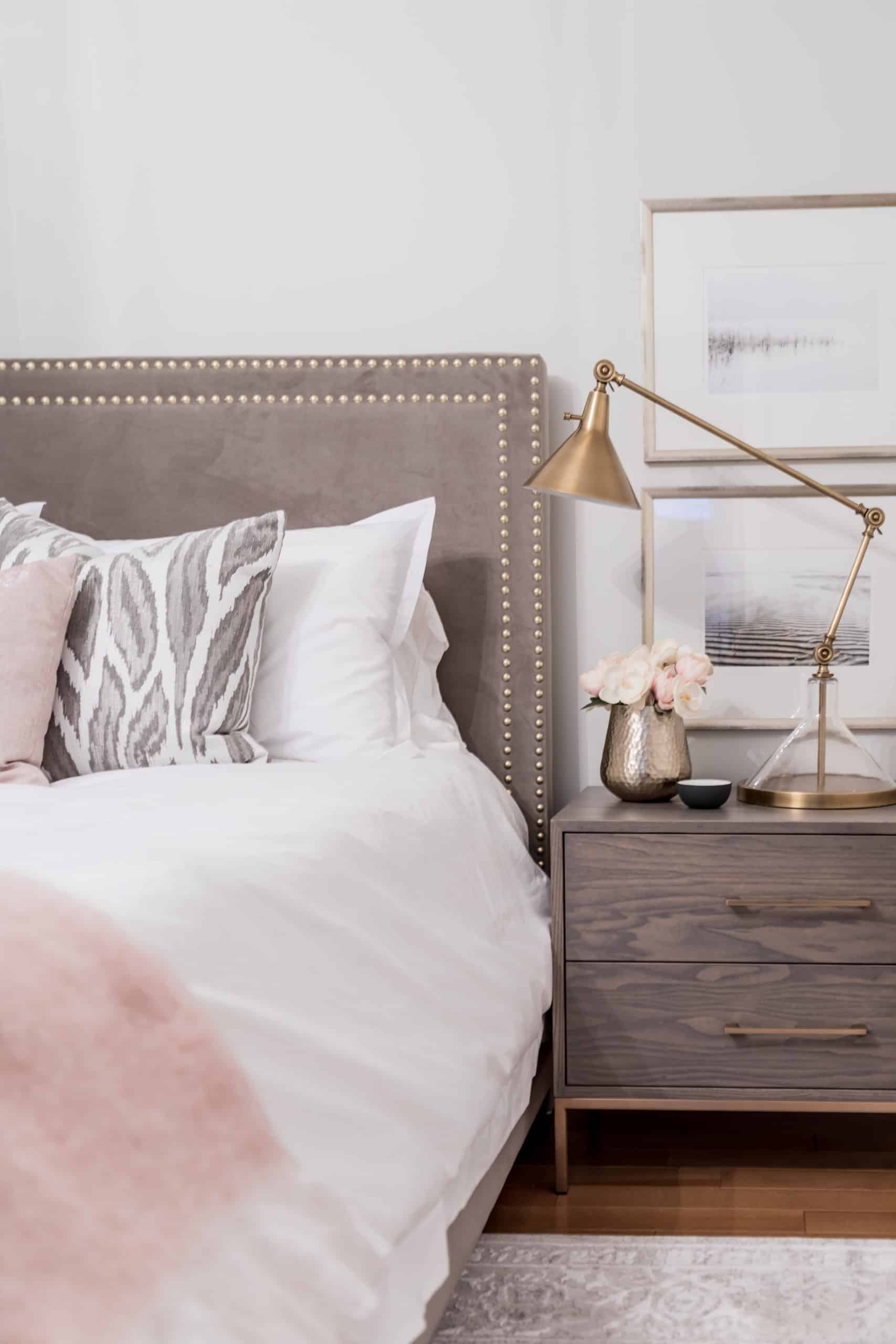 Wooden bedside table with a tall work lamp on it