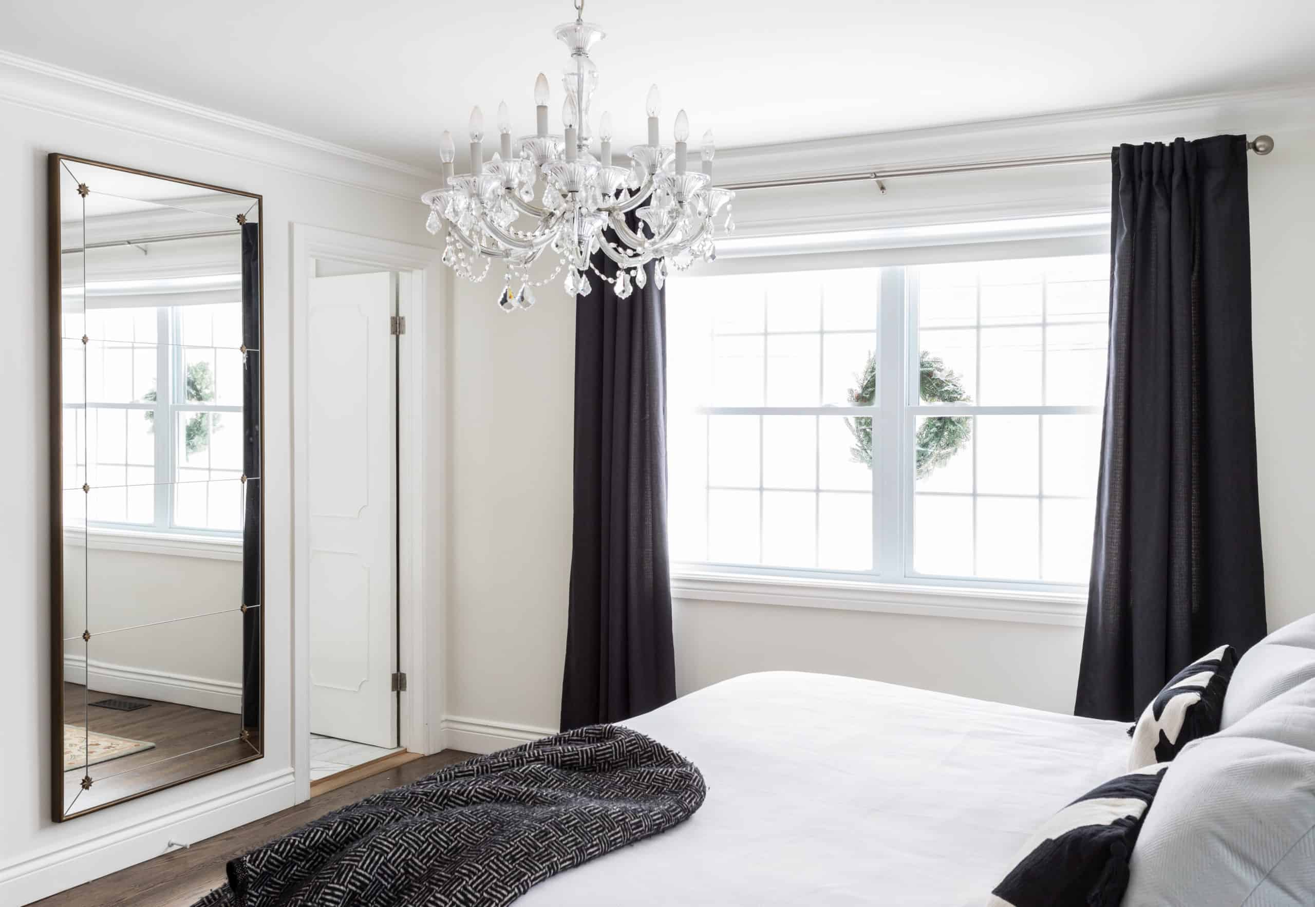 Modern master bedroom with a fancy, white chandelier