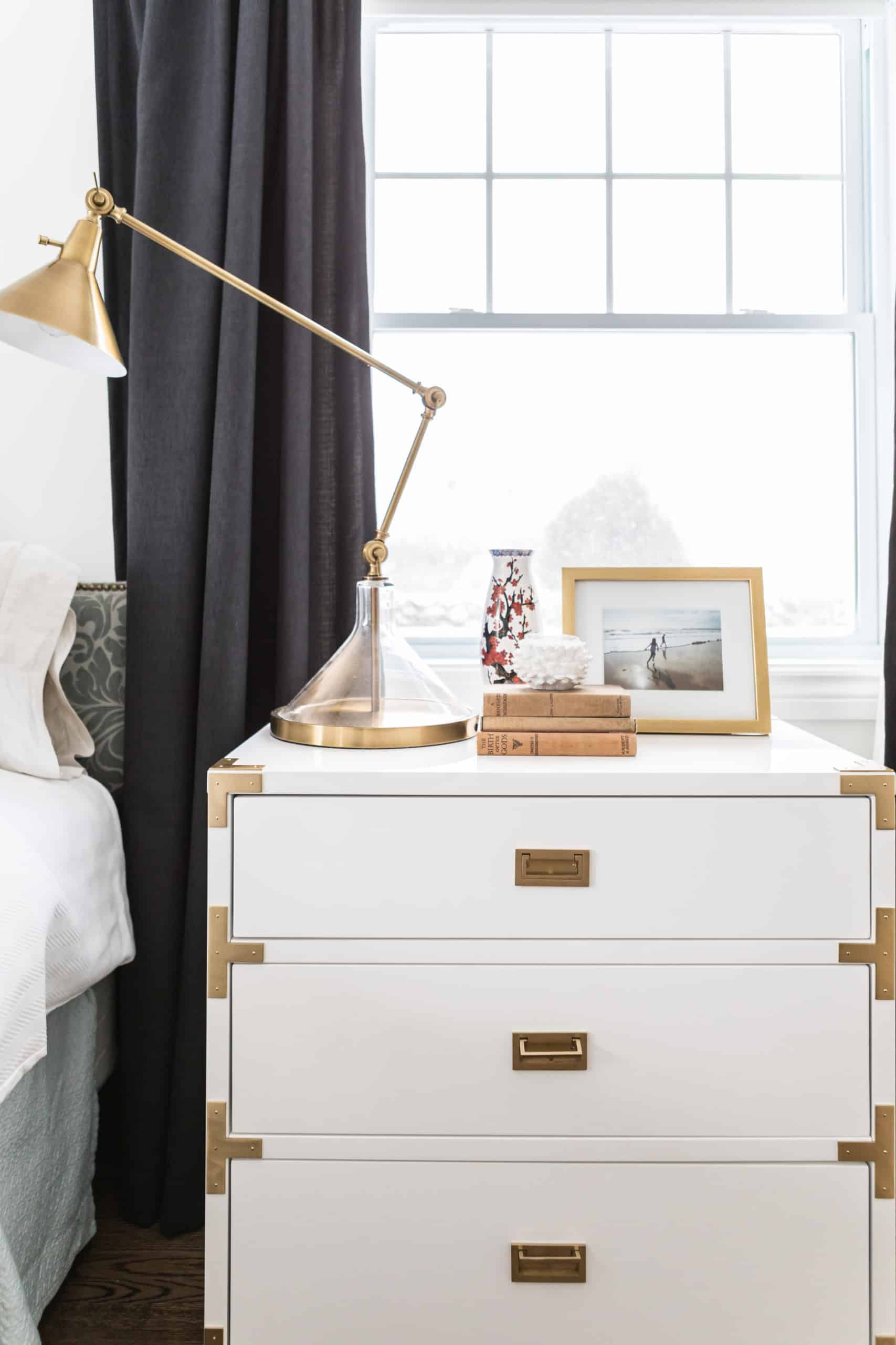 White bedside table with a tall work lamp on it