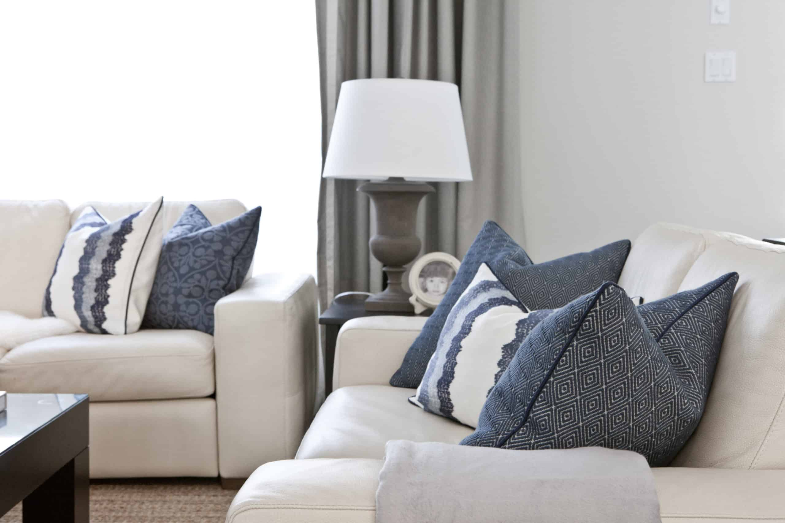 Blue pillows at the end of a white couch