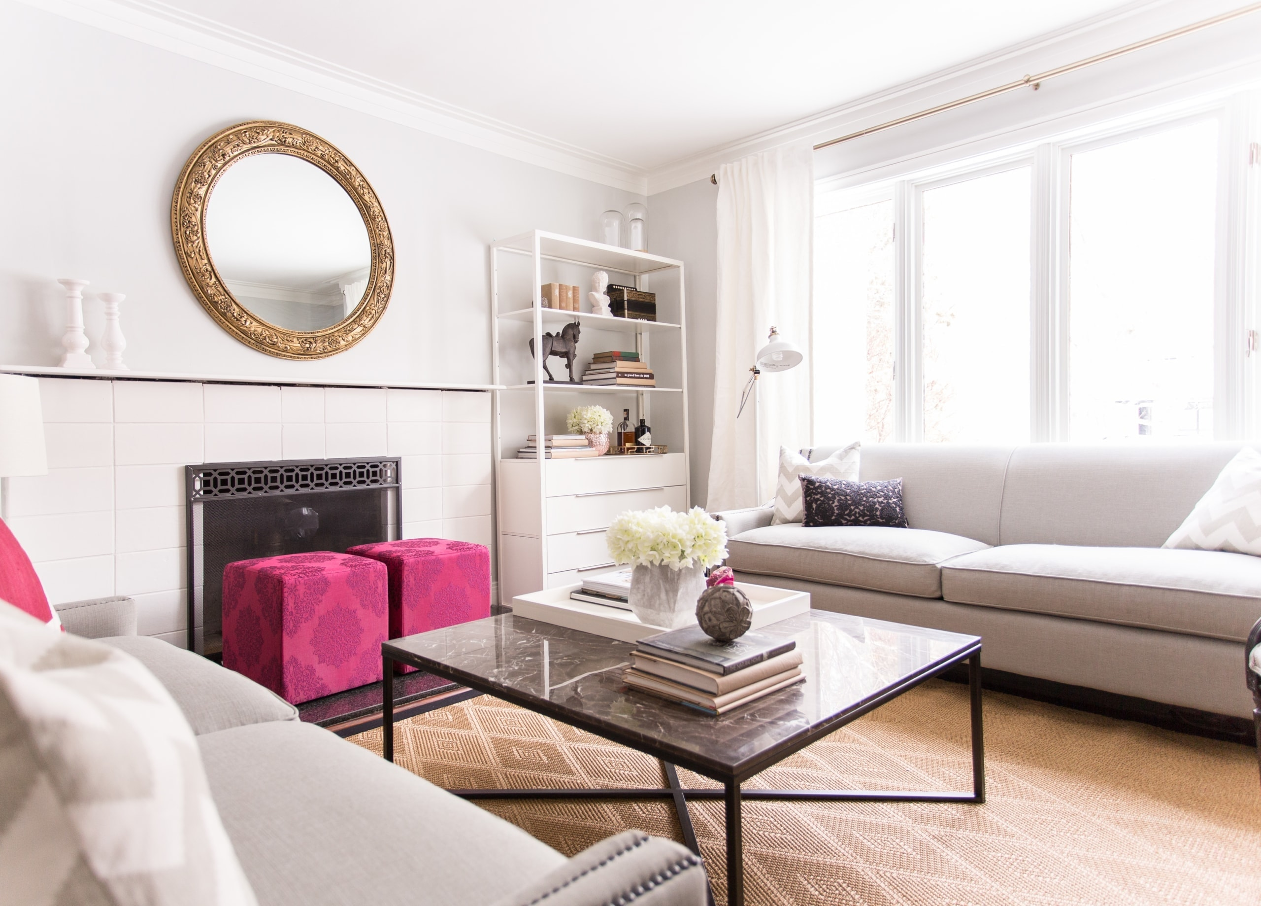 Large, open living room with pink stools next to the fireplace