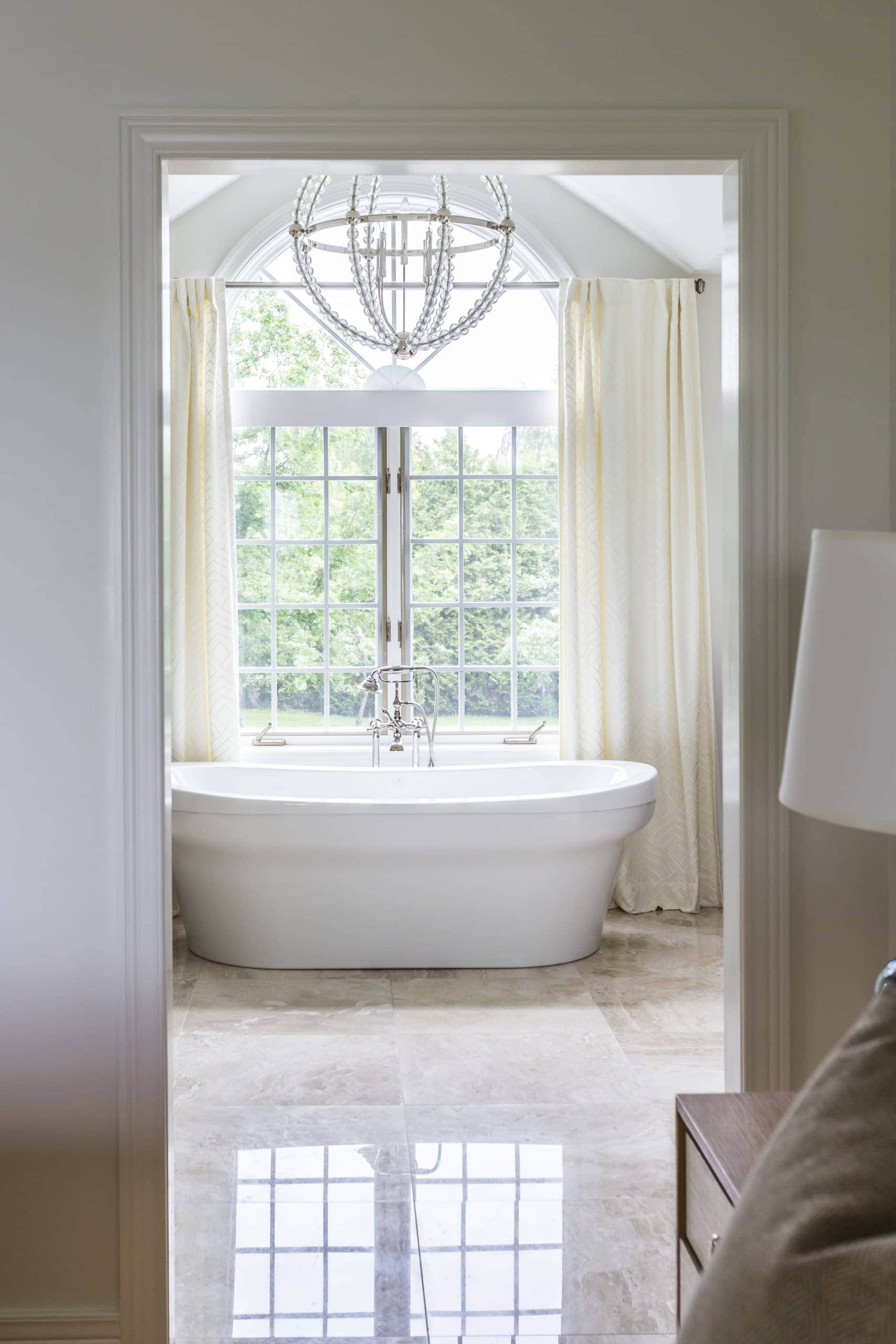 Soaker tub with with a window above it inside a bathroom