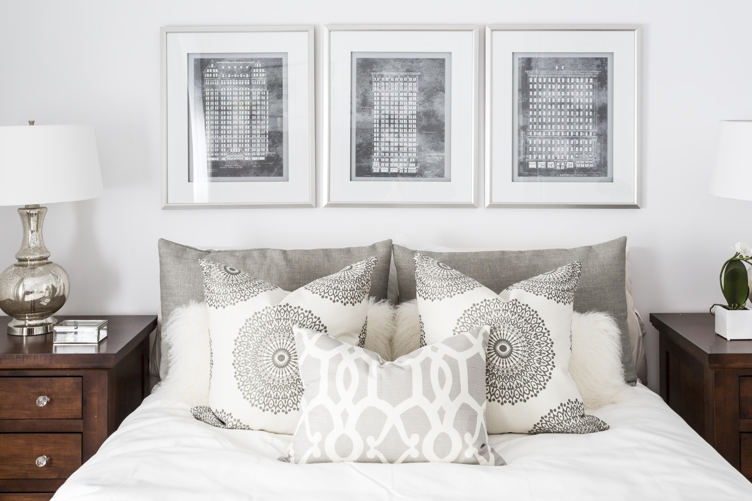 Large bed with three similar pictures above it