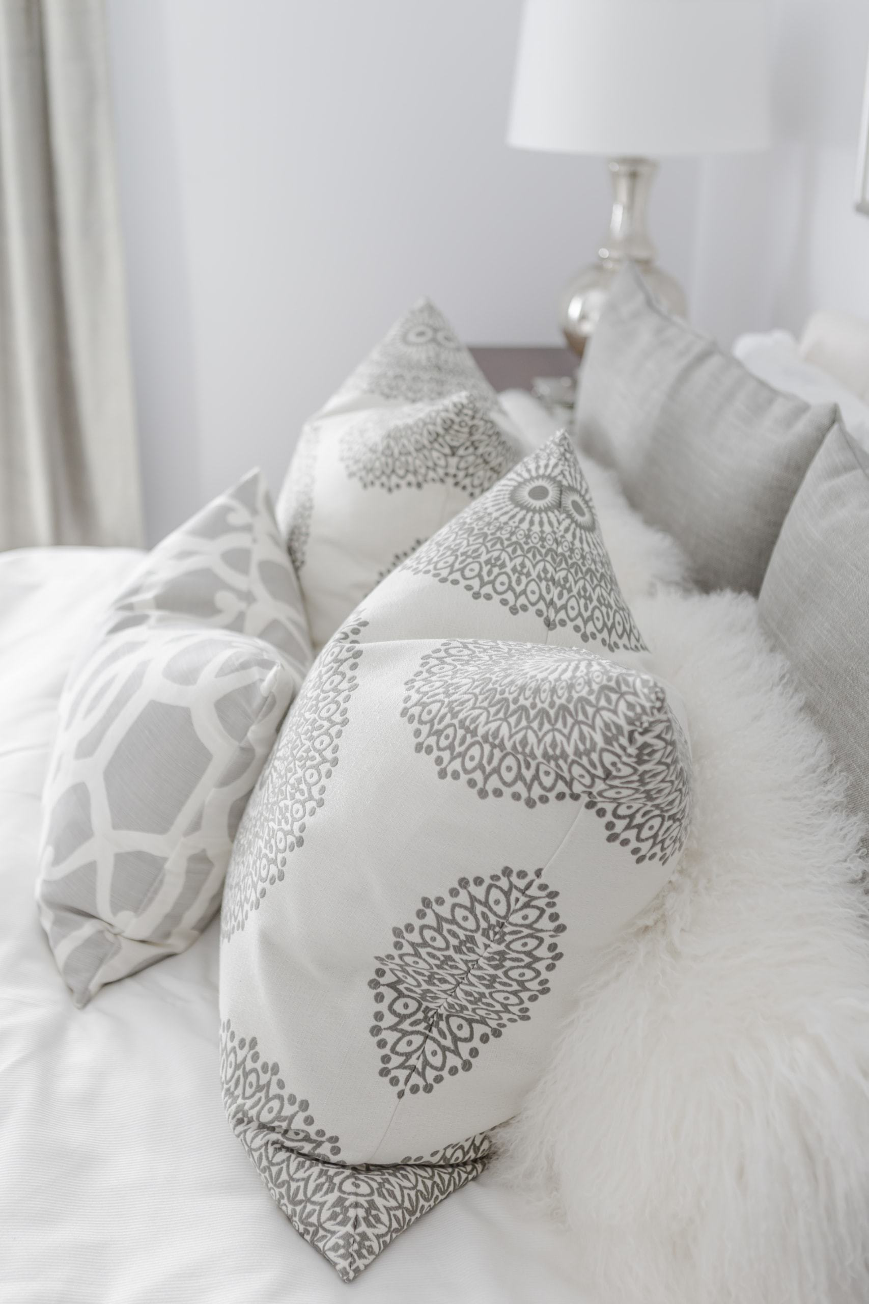 Gray and white pillows on a bed