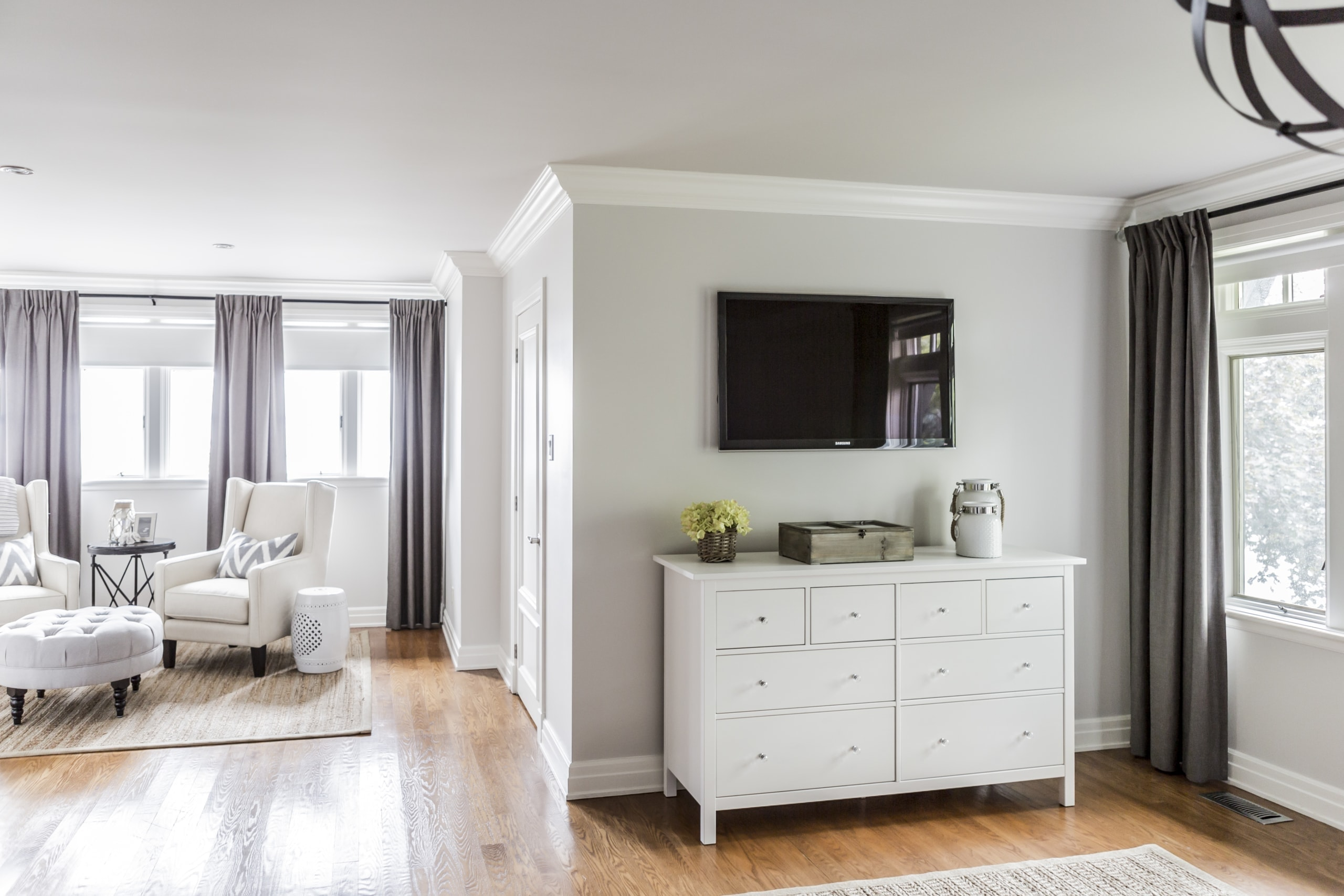 White dresser with a television above it