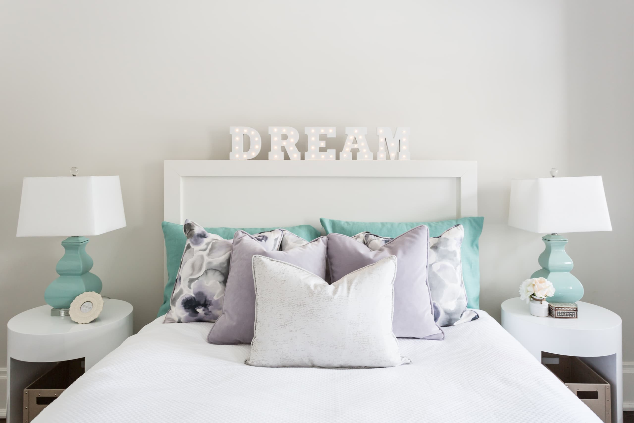 Unsaturated purple bed with the word dream on the headboard