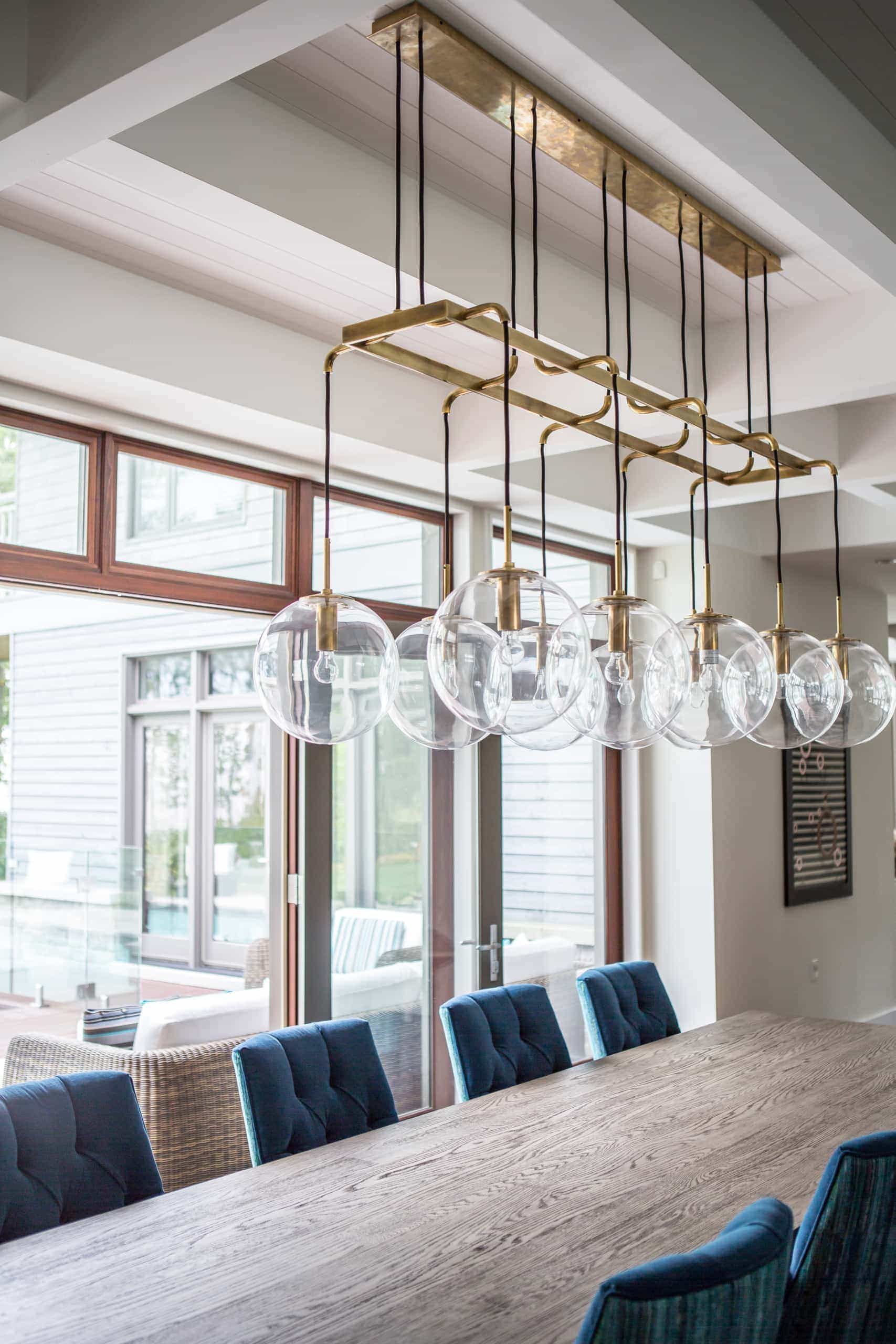 Long dining room table with large ball lights on the chandelier