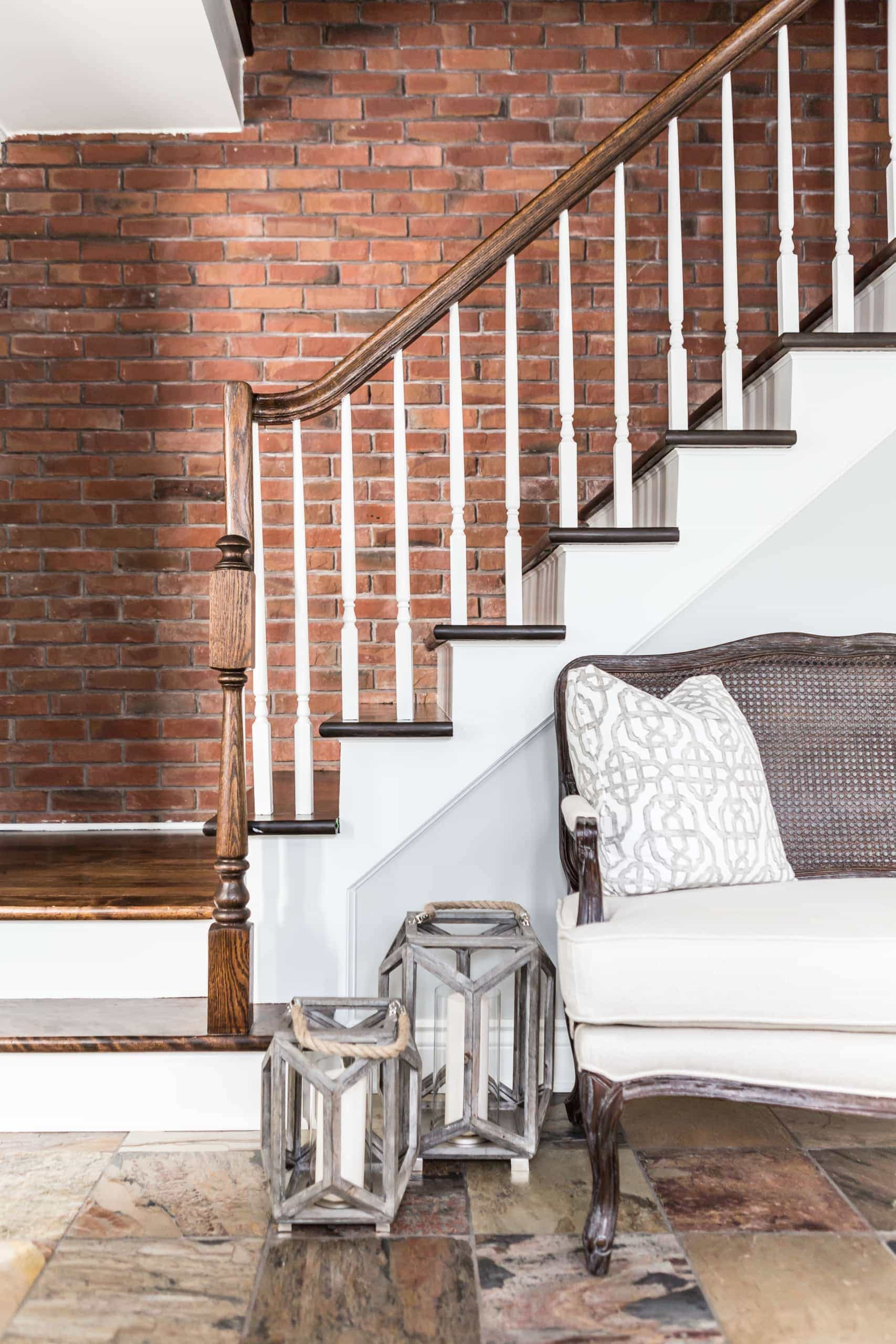 Stairs with a brick accent wall