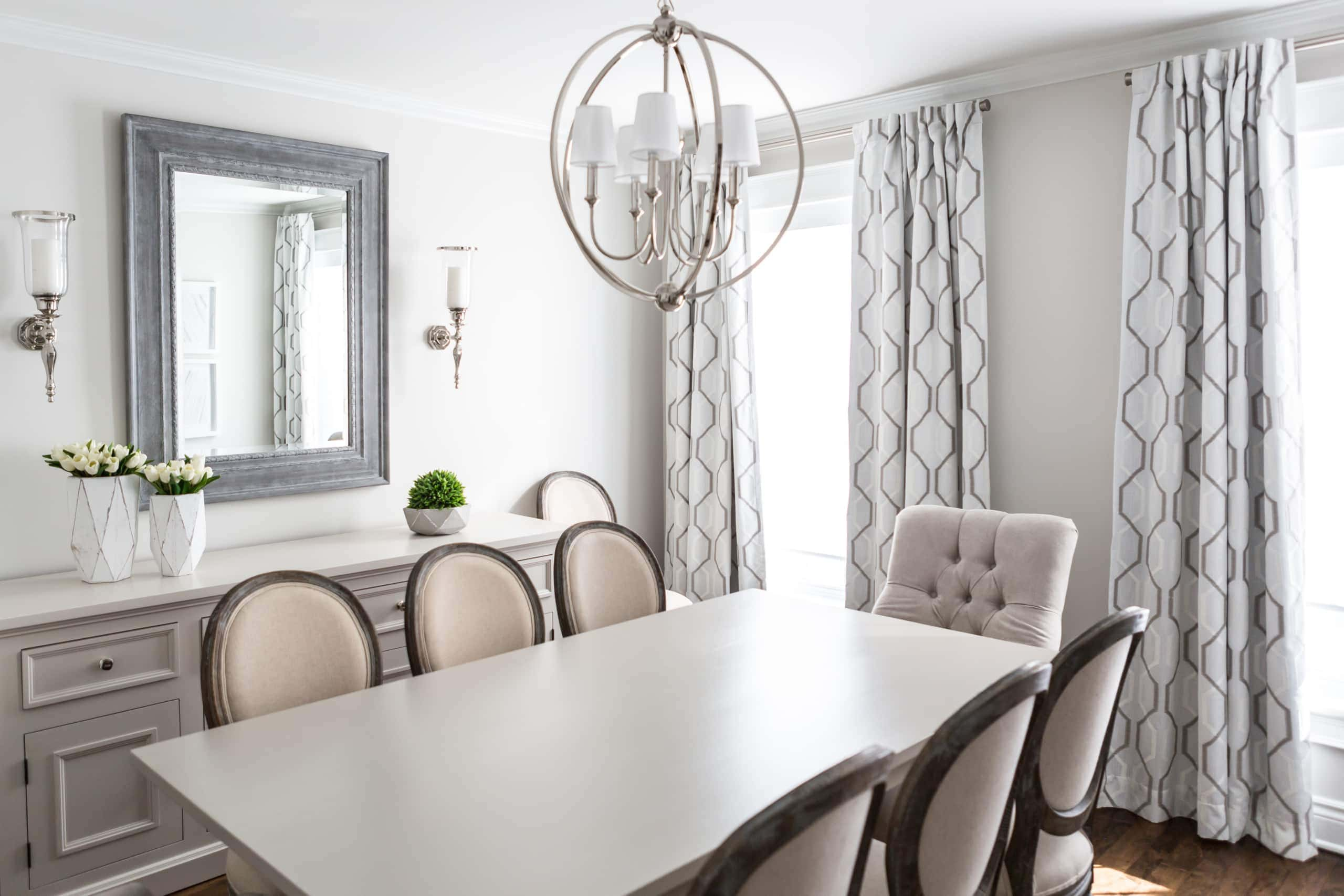 Bright, white dining room with a focus on the table and chandelier