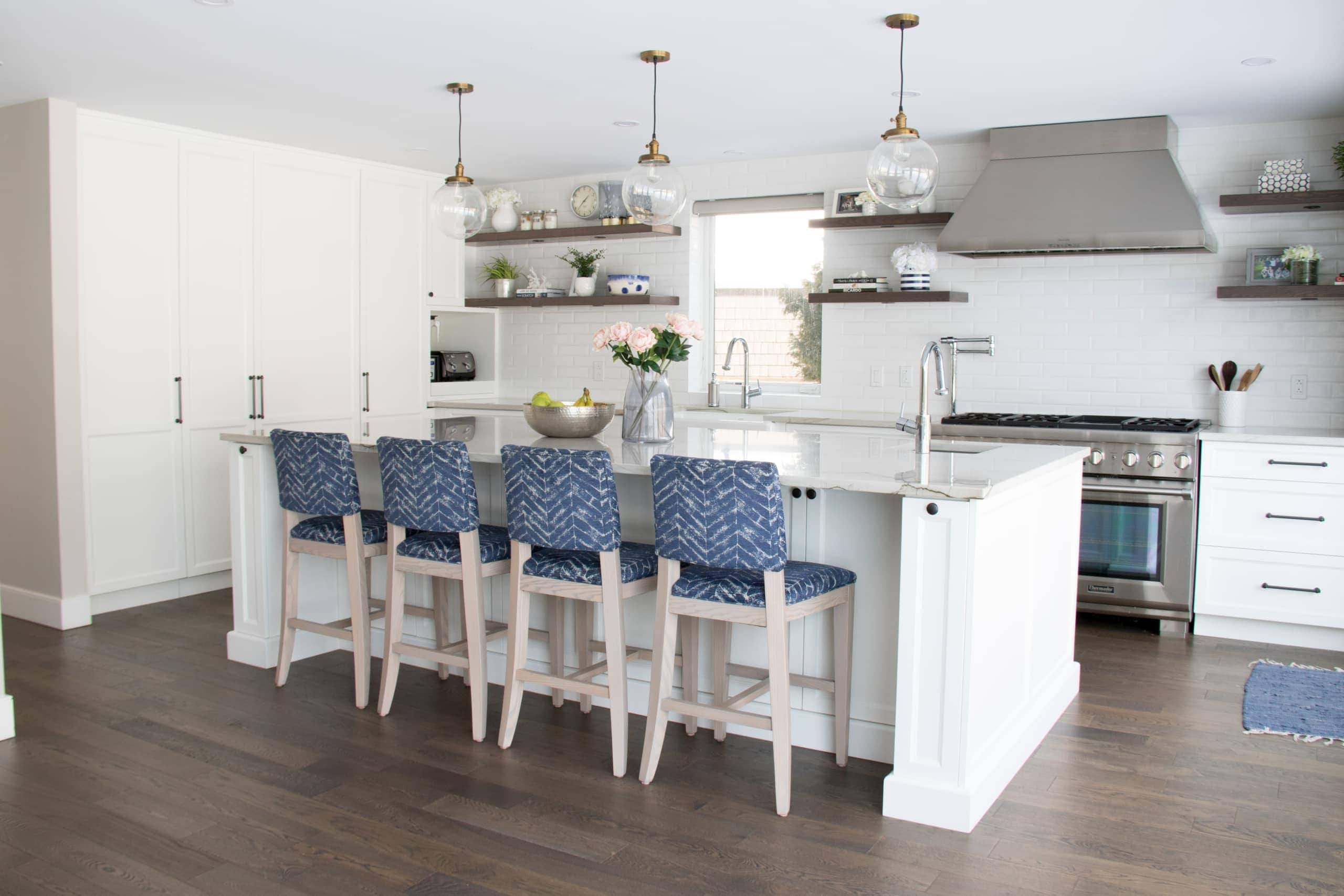 Blue bar stools and an island within a kitchen