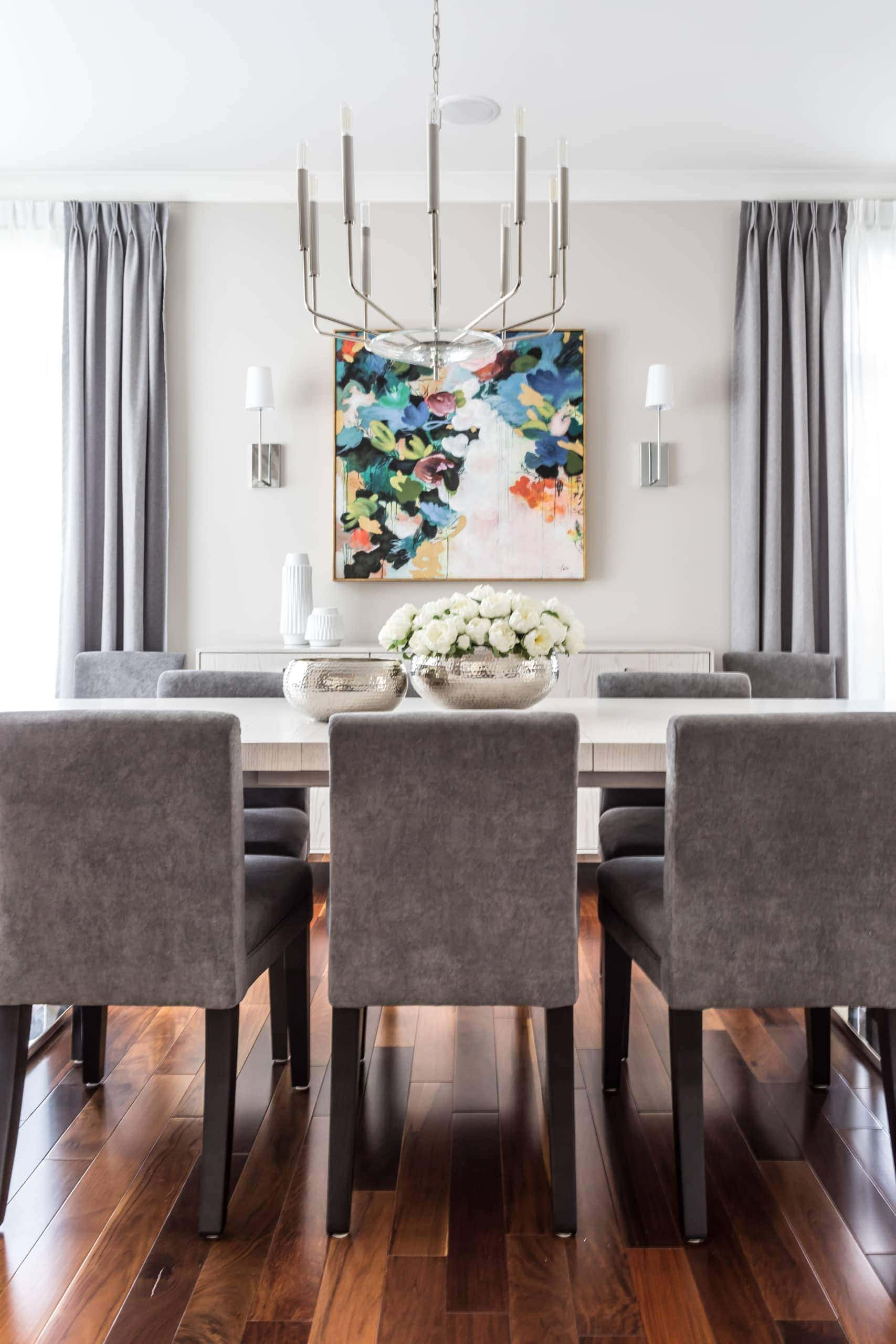 Modern, clean dining room with a low chandelier above the table