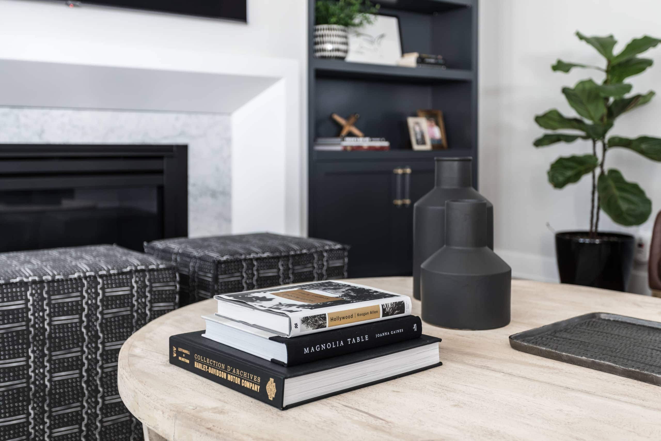 Three books on a round wooden table