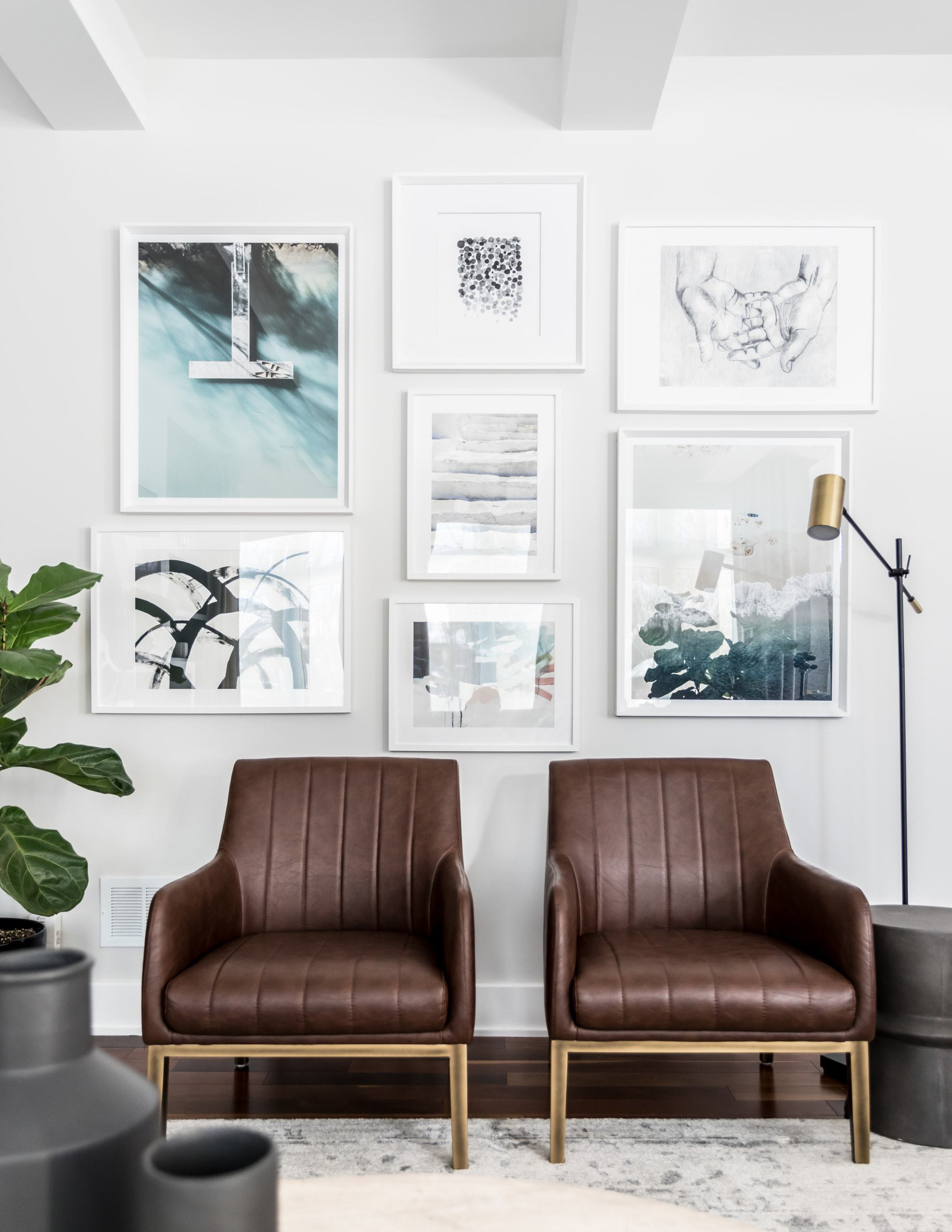 Two brown chairs with some picture on the wall behind them