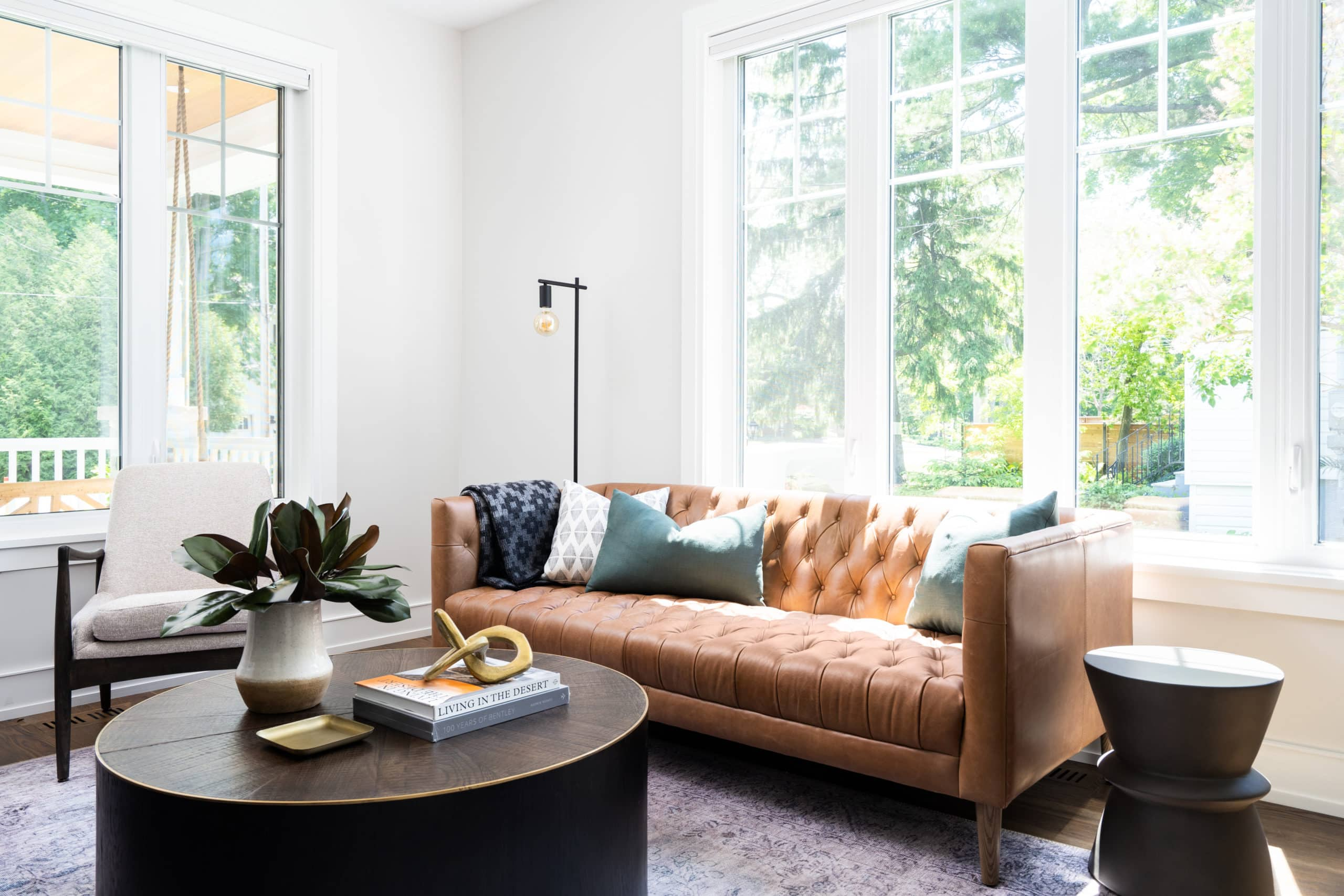 Modern living room with an orange couch and a circular coffee table
