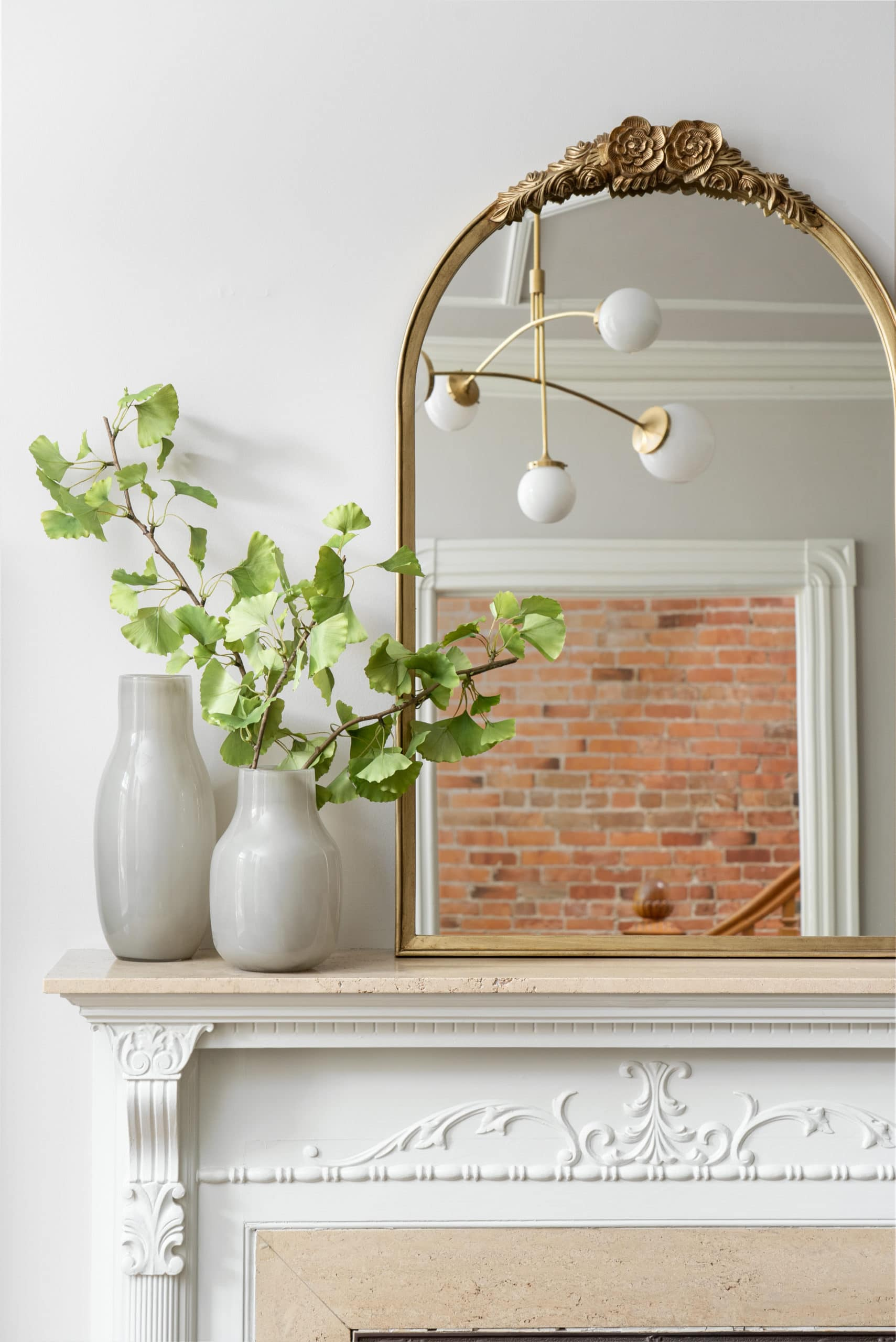Modern fireplace with a mirror and a couple of potted plants on it