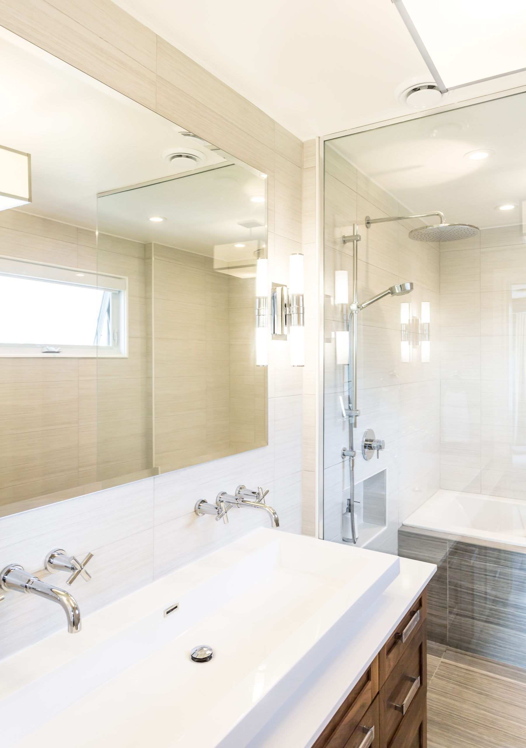 Bright, clean bathroom with a two faucet sink