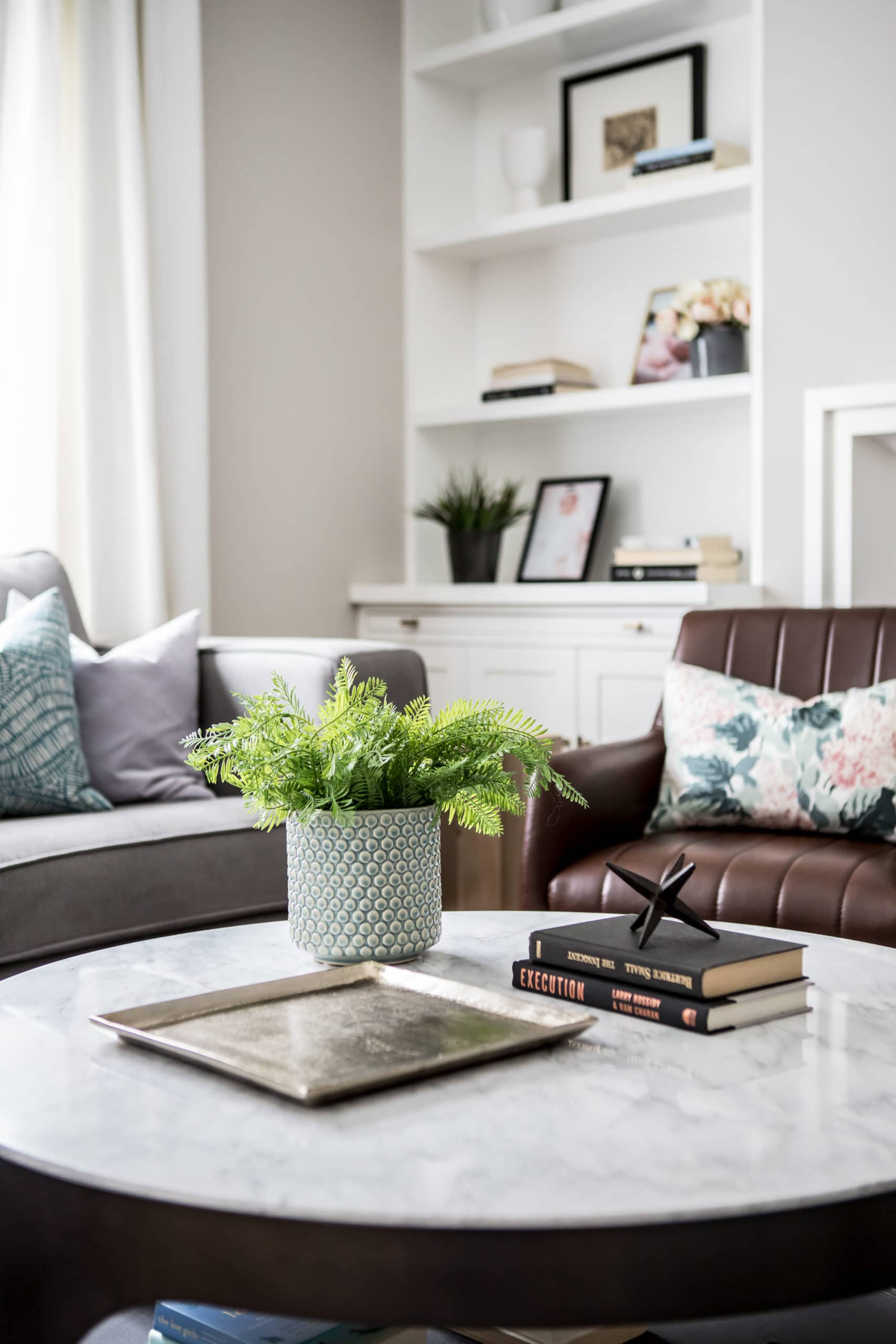 Round table with a potted plant on it in a living room