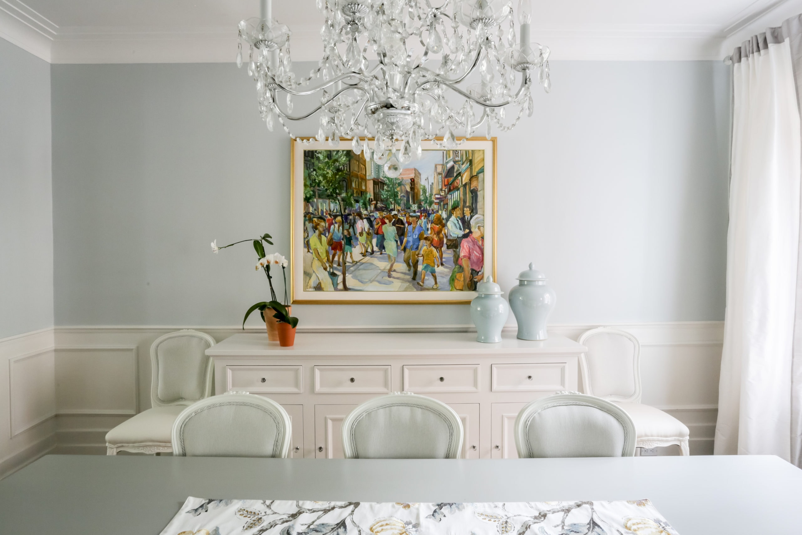 Bright dining room with a painting of a crowded street