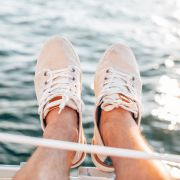 Man wearing Toms shoes hanging off the side of a sail boat over water