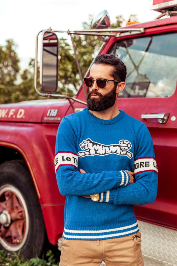 Michael Checkers wearing Le Tigre Retro New blue varsity sweater in front of a vintage fire truck in Miami