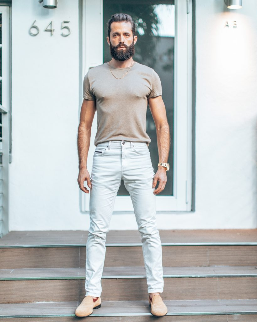 Michael Checkers wearing a light khaki t-shirt and white pants men's fashion trend spring 2020