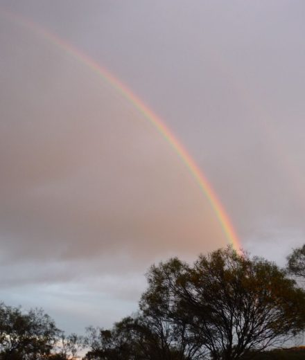An early morning rainbow, coloured by the orange sunlight of the dawn light with a faint secondary rainbow