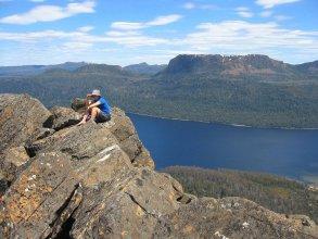 A climber on the summit of Mt. Ida, Lake St. Clair below, Tasmania