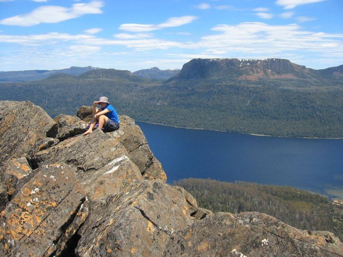 A climber on the summit of Mt. Ida, Lake St. Clair below, Tasmania
