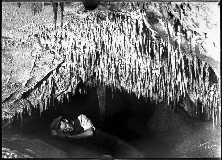 Frank Moon lying underneath some stalactites, Buchan Caves, Victoria - by John Flynn
