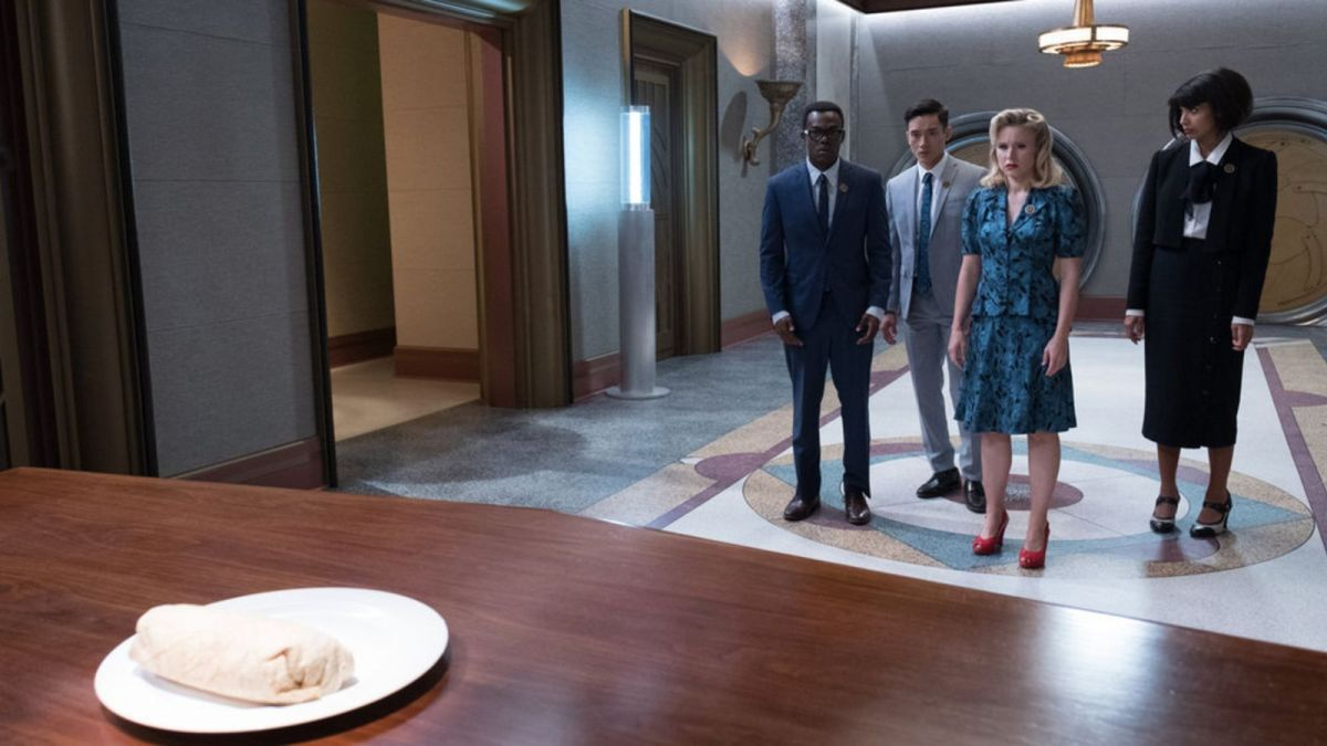 From left to right: Chidi, Jason, Eleanor, and Tahani. They are all staring at a burrito thinking it is the judge of the good place and bad place.