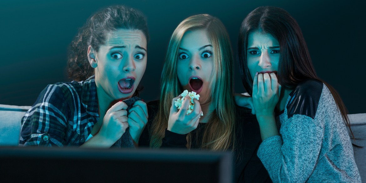 Teenage girls looking scared in front of a TV.