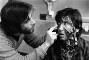 Rick baker applying prosthetics to Griffin Dunne to make it look as if his throat has been torn open by a monster.