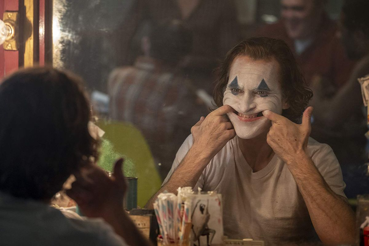 Joaquin Phoenix as Arthur looking into the mirror with clown make up forcing himself to smile.