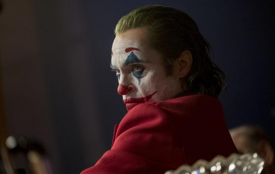 Joaquin Phoenix as the Joker staring menacingly at Murray.