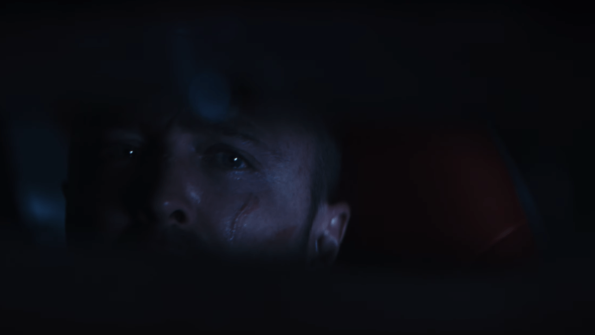 Jesse Pinkman looks in the rearview mirror of a car.