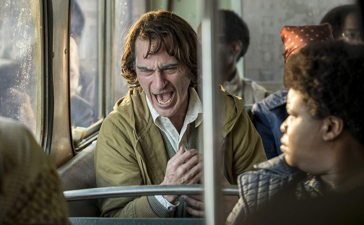 Joaquin Phoenix as Arthur having an episode of pseudobulbar affect on the bus with onlookers.