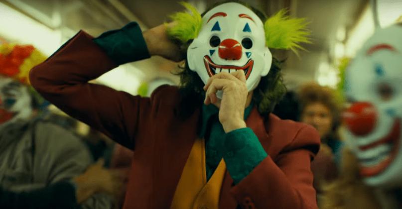 Joaquin Phoenix as the Joker donning a clown mask over his clown makeup.