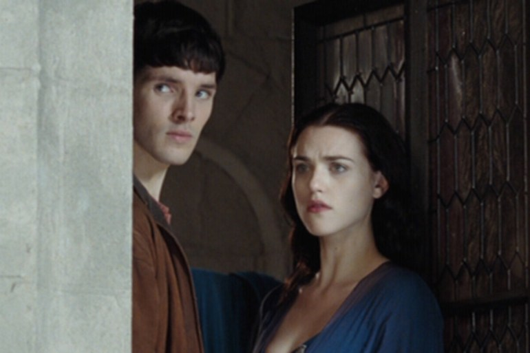 merlin and morgana stand at a window in the castle