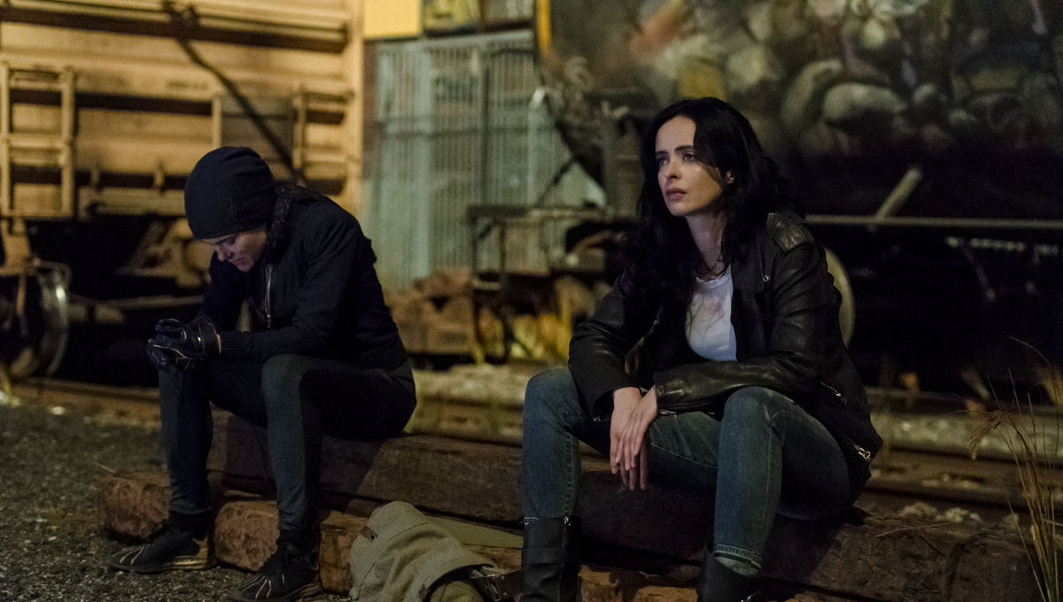 Jessica Jones sitting next to someone in the series Marvel's Jessica Jones on Netflix.