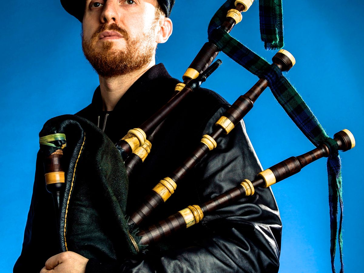 Griogair looking off into the distance while holding bagpipes.