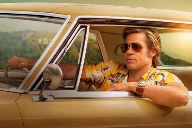 Brad Pitt as Cliff Booth driving yellow car in Once Upon a Time in Hollywood.