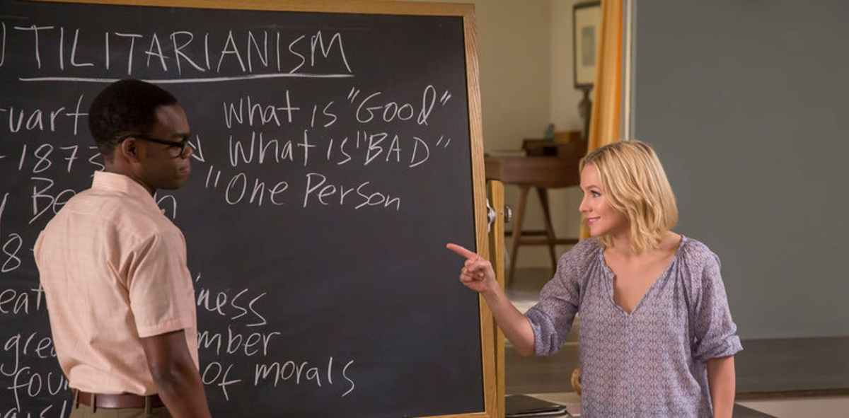 Eleanor draws motivation from Chidi while they stand in front of a black board that has ethics lesson written on it.