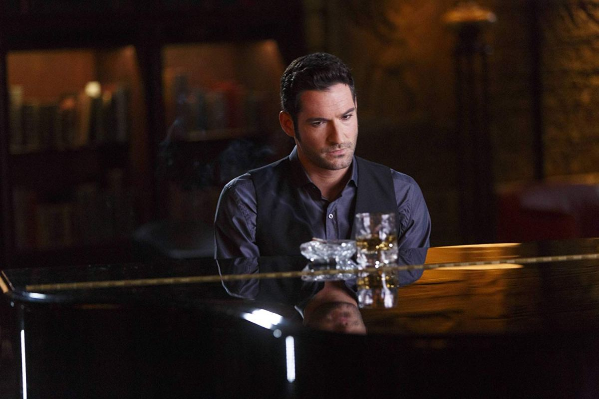 Lucifer Morningstar sits at a piano.