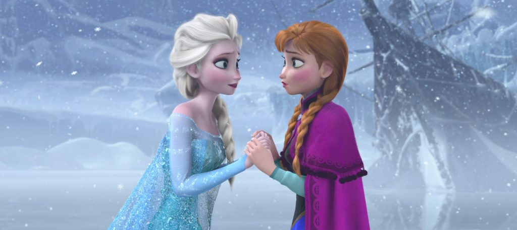 Princesses Elsa and Anna holding each others hands in the snow.