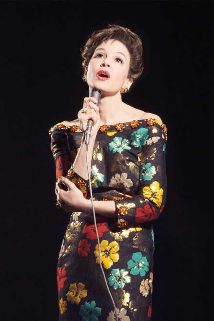 Renee Zellweger as Judy Garland sings in a pretty floral dress. Her believable performance a guarantee to win at the oscars.