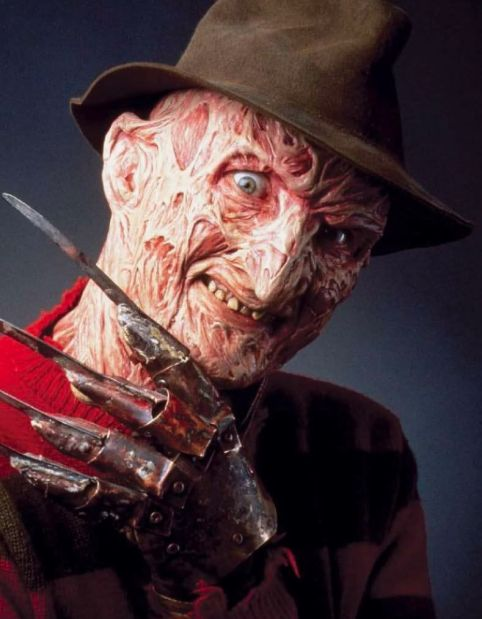 Freddy Kreuger the monster from Nightmare on Elm street poses with his clawed glove. He looks flayed and gruesome.