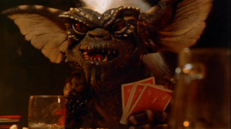 Spike the monster from Gremlins sits at a table with playing cards and a drink. His large green ears look like bat wings. His white tuff of a mohawk is placed on top of a scaly, ugly face.