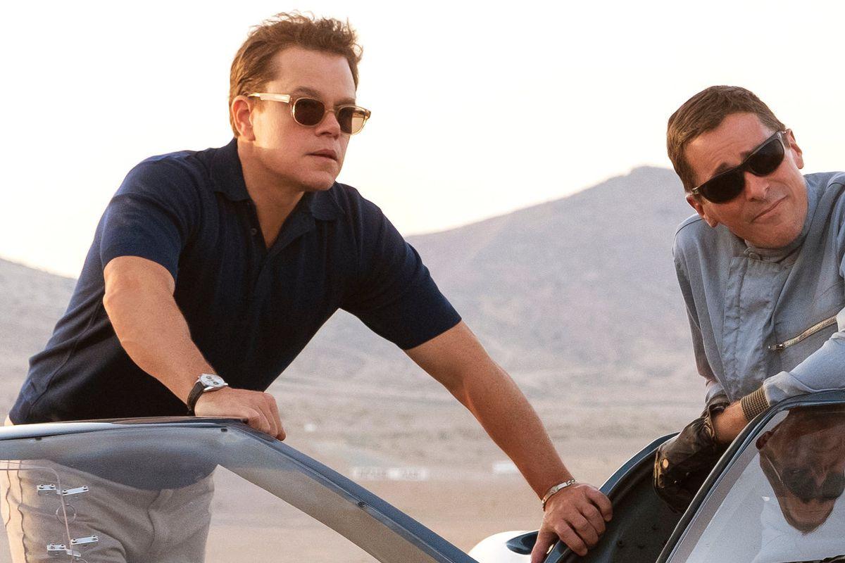 Matt Damon and Christian Bale leaning on a car.