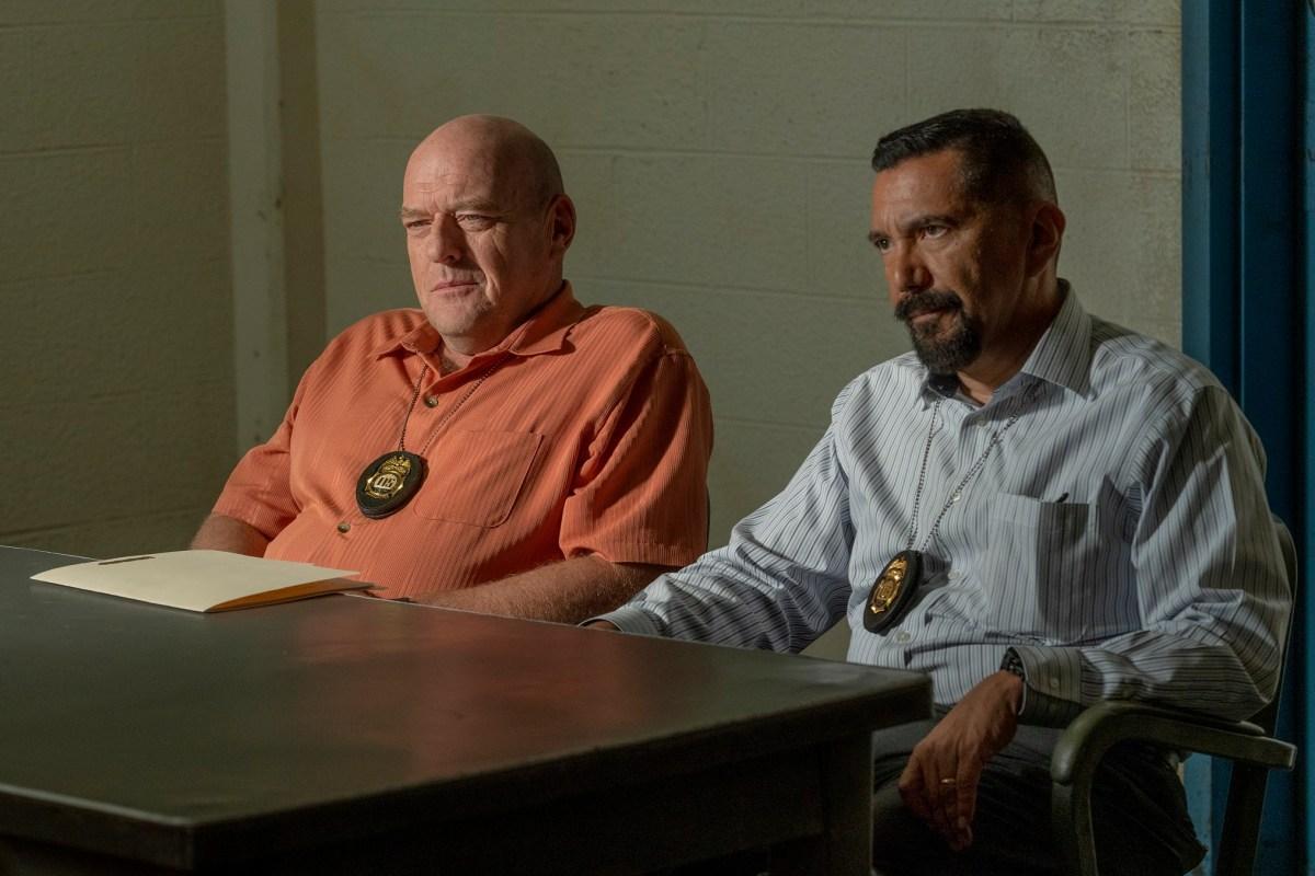 DEA agents Hank Schrader and Steve Gomez sit behind an interrogation table.