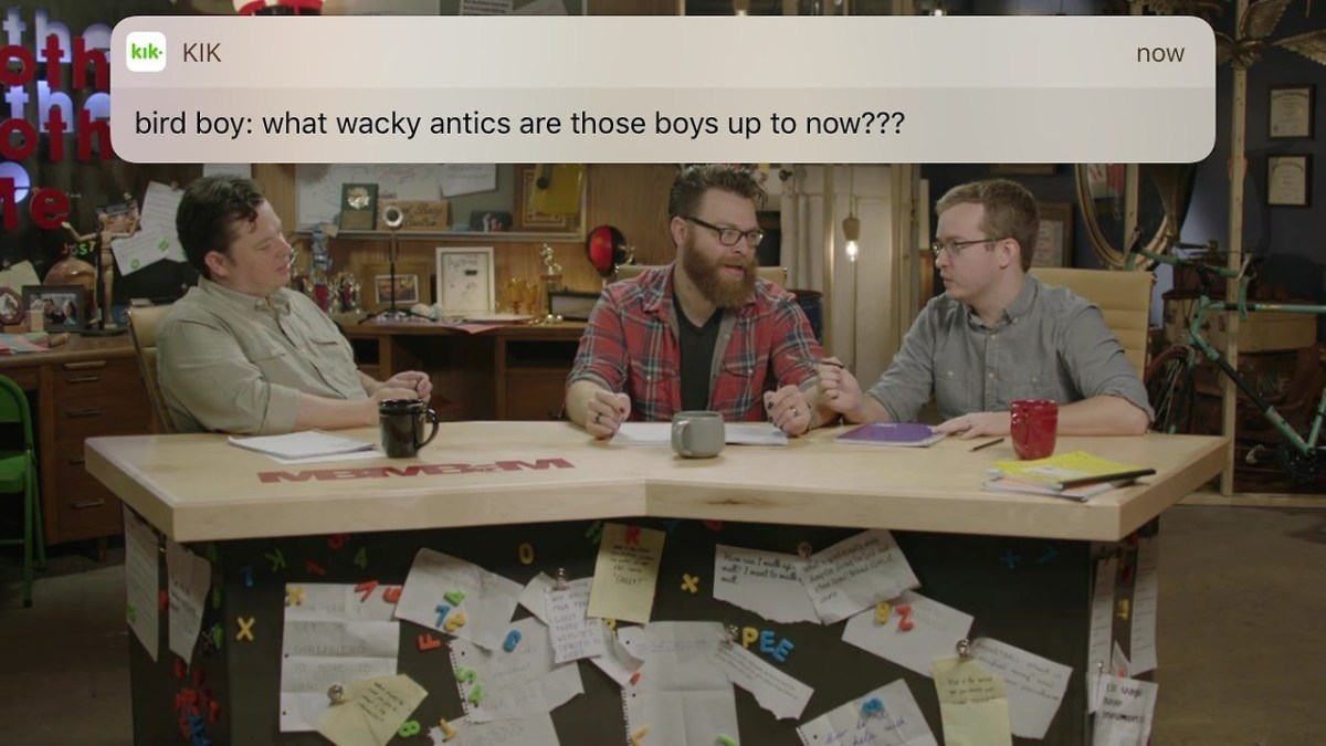 MBMBaM television show with all three brothers at their desk.